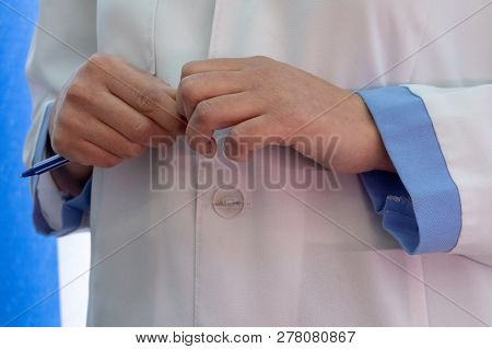 A woman in a white lab coat with blue cuffs. Female doctor hands with pan. stock photo
