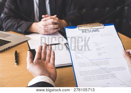 Employer or recruiter holding reading a resume during about his profile of candidate, employer in suit is conducting a job interview, manager resource employment and recruitment concept. stock photo