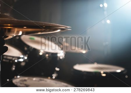 Close-up Drum set in a dark room against the backdrop of the spotlight. Atmospheric background symbol of playing rock or jazz drums. Copper plates on a cold background stock photo