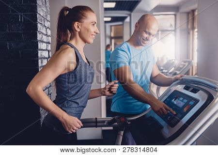 Personal training with a trainer on a treadmill. The trainer controls the correctness of the exercise when using a treadmill for cardio. Control coach in the gym. Athletic jogging with a trainer stock photo