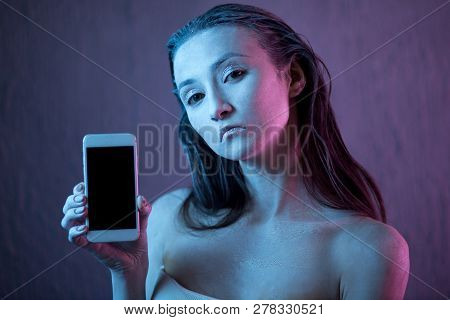 young scared and worried girl holding mobile phone as internet stalked victim abused and cyberbullying or cyber bullying stress concept in black stock photo