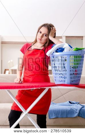 Young beautiful woman ironing at home   stock photo