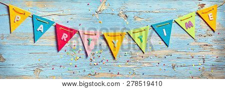 Karneval - Carnival - themed festive party banner background with triangular rainbow colored bunting and streamers forming a border on blue wood with colorful confetti stock photo