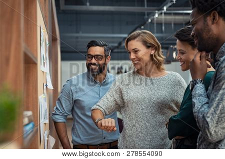 Group of mature businesspeople planning business strategy while looking at infographic on wall. Busi