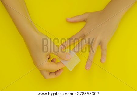Woman Hands Care. Varnish removal Small nail art and manicure business. Top View Of Beautiful Smooth Womans Hands With Professional Nail Care Tools For Manicure On yellow Background. Closeup Of Healthy Female Nails With yellow Nail Polish stock photo
