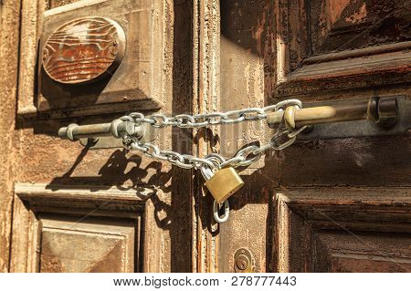 Metal chain with a lock on an old wooden door, close-up stock photo