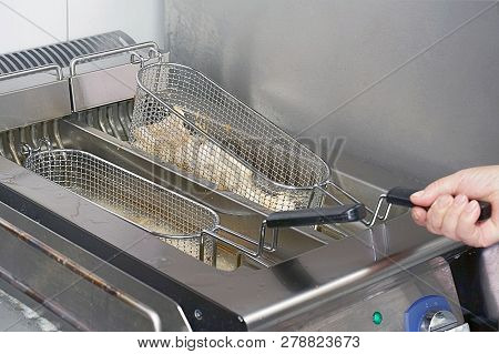 The cook fries fish in a deep fryer. Preparation in a deep fryer. Deep fryer with boiling oil on restaurant hotel kitchen stock photo