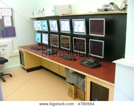 An image showing a CCTV control room desk with many monitors stock photo