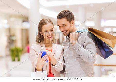 sale, consumerism, technology and people concept - happy young couple with shopping bags and smartph