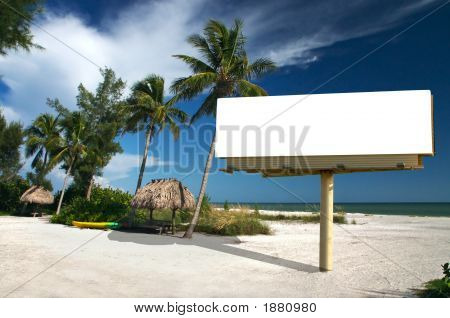 Tropical beach setting with a place to eat - included is a white billboard for you to place text or an advertisement - maybe for a travel ad? stock photo