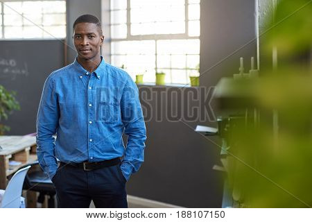 Portrait of a focused and confident young African businessman while standing with his hands in his pockets in a large modern office stock photo
