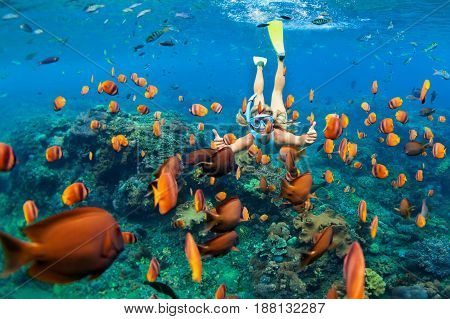 Happy family - girl in snorkeling mask dive underwater with tropical fishes in coral reef sea pool. Travel lifestyle water sport outdoor adventure swimming lessons on summer beach holiday with child