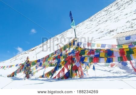 Prayer flags is a colorful rectangular cloth often found strung along mountain ridges and peaks high in the Himalayas in Chang la pass road Leh India stock photo