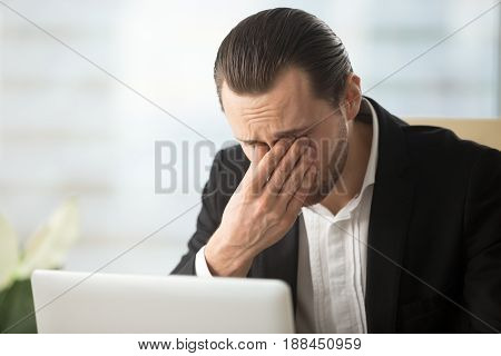 Frustrated businessman feels pain in eyes because of eyesight overstrain after long computer work. Tired young man massaging eyes in front of laptop. Eyes fatigue, headache or dizziness at workplace stock photo