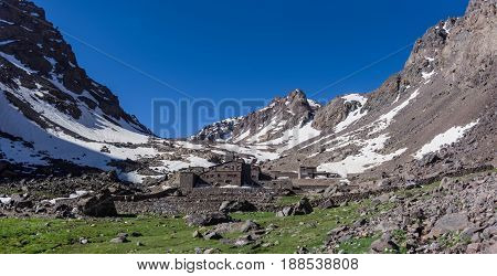 Toubkal national park in springtime with mount cover by snow and ice Refuge Toubkal start point for hike to Jebel Toubkal – highest peak of Atlas mountains and Morocco stock photo