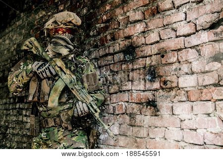 Operator of Russian special operations forces with kalashnikov assault rifle and combat helmet in ruined buliding during military operation in Syria. Bullet holes on the wall stock photo