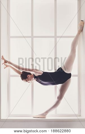 Ballerina. Classical Ballet dancer in standing split on window