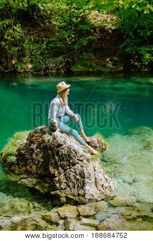 woman relax at mountain lake view. Auhentic Blonde woman travel in Montenegro Skakavice Oko. stock photo