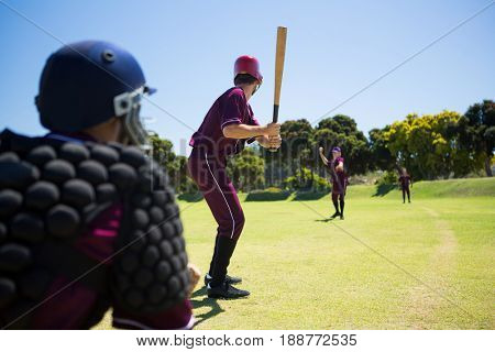 Players playing baseball together on field against clear blue sky stock photo