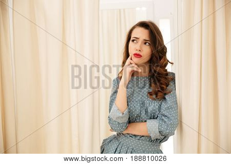 Picture of thinking young lady standing in fitting room. Looking aside. stock photo