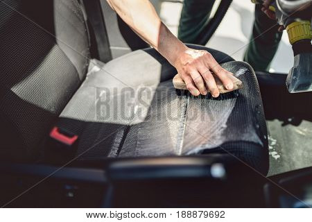 Car care concept detailing and cleaning details. Worker using cleansing techonology for upholstery stock photo