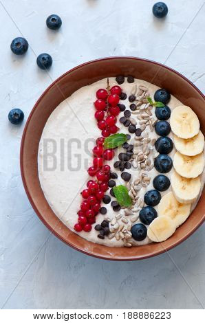 Healthy oat smoothie with bananas and cottage cheese garnished with red currants sunflower seeds chocolate drops and blueberries in a bowl on a white stone background. stock photo