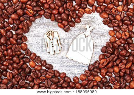 Cardboard tuxedo and dress. Heart from coffee beans. stock photo