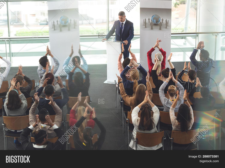 acclaiming,achievement,adviser,african ethnicity,applauding,appreciate,asian,asian ethnicity,associate,black,business,businessman,businesswoman,caucasian,caucasian ethnicity,celebrating,colleagues,conference,confidence,consultant,executive,explaining,female,formals,leadership,male,man,mature adult,mature men,mature women,microphone,mid adult,mid adult men,mixed-race,mixed-race person,presentation,seminar,sitting,smart casual,speaker,speaking,standing,success,suit,training,woman,young adult,young men,young women