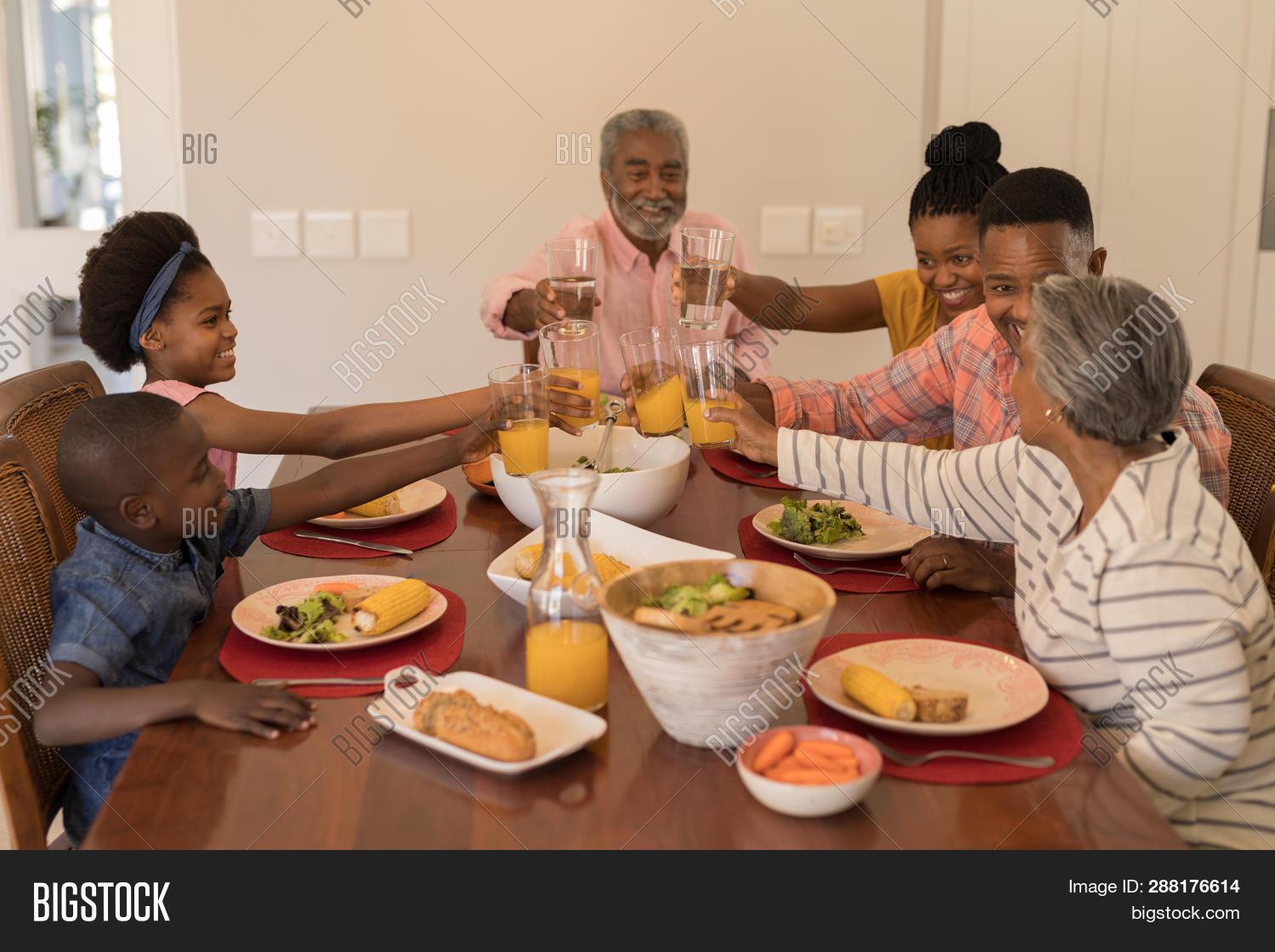 Multi-generation African American family toasting glasses of orange juice and water while sitting at the dining table at home