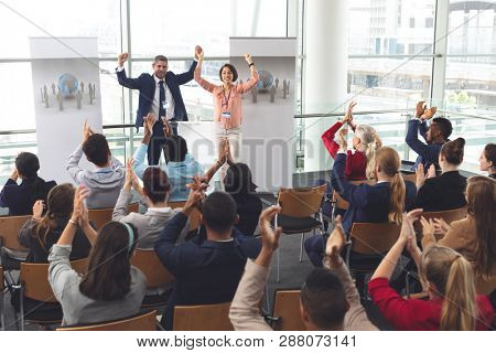Rear view of diverse business people applauding and celebrating while they are sitting in front of multi-ethnic business executives holding arms up in the air at business seminar in office building stock photo