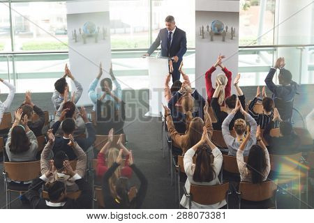 High angle view of diverse business people applauding while they are sitting in front of mixed race businessman at business seminar in modern office building stock photo