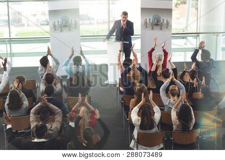 High angle view of diverse business people applauding mixed race businessman after successful presentation at business seminar  stock photo