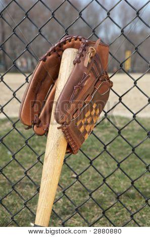 Baseball glove on bat leaning on fence at ballpark stock photo