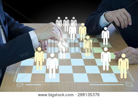 Three business administrators playing checkers or draughts on a wooden virtual checkerboad or draughtboard in concept of manpower or human resource strategy planning to form a teamwork. stock photo