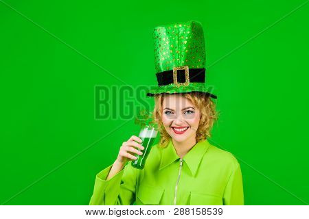 Woman celebrating St. Patrick's Day with beer. Beautiful girl in green leprechaun hat drinking green beer. St. Patrick's Day celebration. Patrick Day pub party. Saint Patrick's day or october festival stock photo
