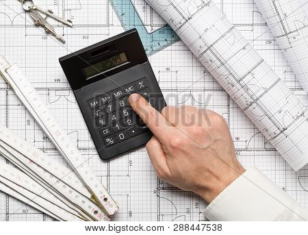 Architect using calculator on architectural blueprint house building plan with pencil, ruler, compasses and square flatlay top view from above stock photo