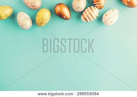 Flat Lay of Golden Easter Eggs in row placed on turquoise background. Easter background or easter concept. stock photo