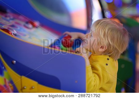 Little boy having fun in amusement in play center. Kid playing on slot machine in Arcade centre. Entertainment industry for childs. stock photo