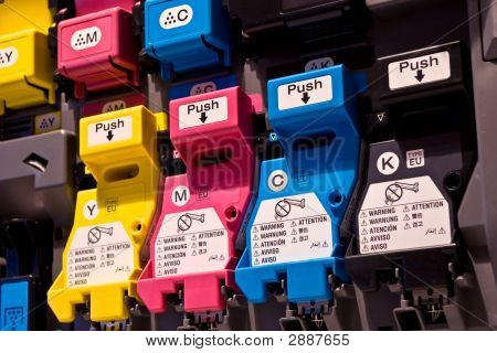 Cyan magenta yellow and key-color cartridges in a printer. stock photo