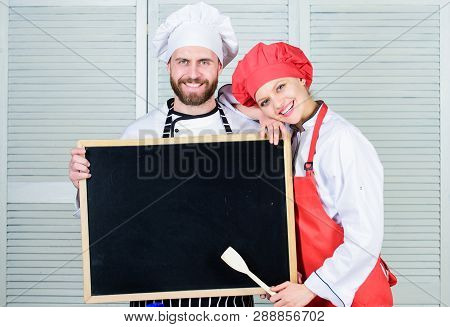 Mastering cooking skills. Couple of man and woman holding empty blackboard in cooking school. Master cook and prep cook giving cooking class. Chef and cook helper teaching master class, copy space stock photo