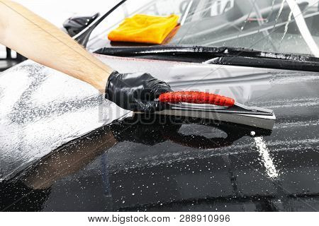 A man cleaning car with plastic sponge. Car detailing or valeting concept. Selective focus. Car detailing. Cleaning with sponge and cloth. Worker cleaning. Car wash concept solution to clean stock photo