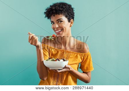 Beautiful young african woman eating fresh salad with tomatoes. Portrait of smiling woman in diet is