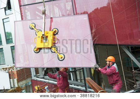 Tho builders worker installing glass windows on facade of business building stock photo