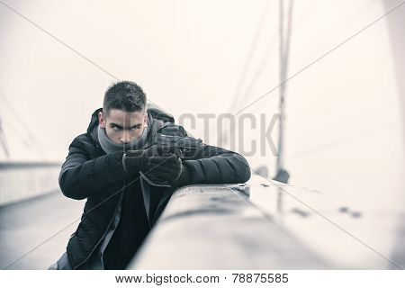 Well dressed handsome young detective or policeman or mobster standing in an urban environment aiming a firearm hiding behind small wall with a determined expression side view stock photo