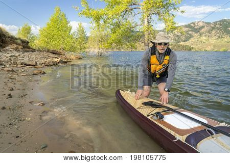 Senior paddler with a large volume expedition stand up paddleboard on a shore of mountain lake - Horsetooth Reservoir in northern Colorado stock photo