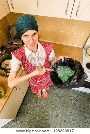 A woman with a scarf on the head and a red apron is looking inside a black trash can with a garbage bag in the kitchen. She is very disturbed by the bad smell stock photo
