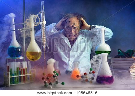 Crazy scientist yelling in his lab front of exploded experiment  stock photo
