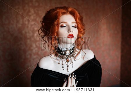 Vampire clothes for Halloween. Girl dress gothic outfit for halloween. Interesting gothic outfit for Halloween. Celebrate Halloween. Prepare an interesting look on Halloween. A woman is a vampire with pale skin and red hair in a black dress and a necklace stock photo