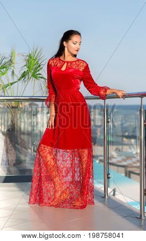 A beautiful young woman in a red dress posing on a light blue sky background. An elegant lady in a saturated scarlet velvet and guipure dress. A gorgeous lady on a hotel terrace. stock photo
