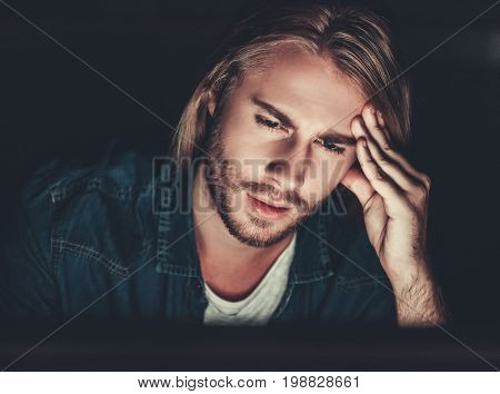 Handsome young businessman with shoulder-length blond hair is working with a computer at night stock photo